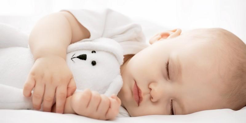 Baby schläft mit Stofftier