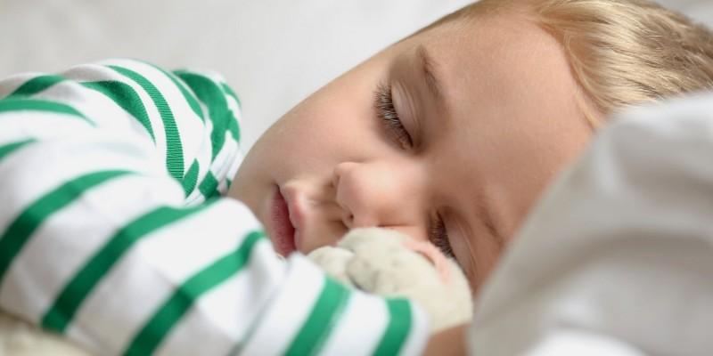 Junge schläft im Kinderbett