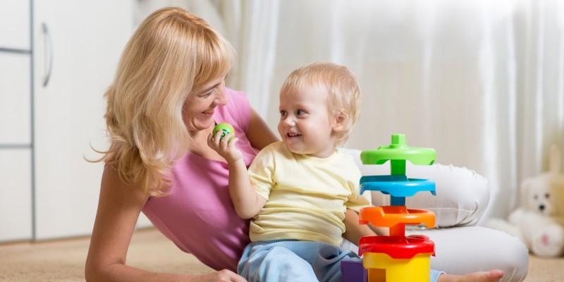Mutter spielt mit Kind am Boden
