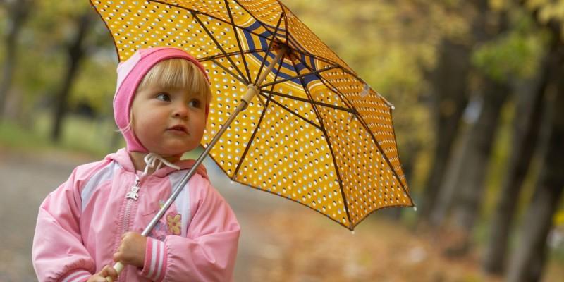 Warm angezogenes Mädchen mit Schirm
