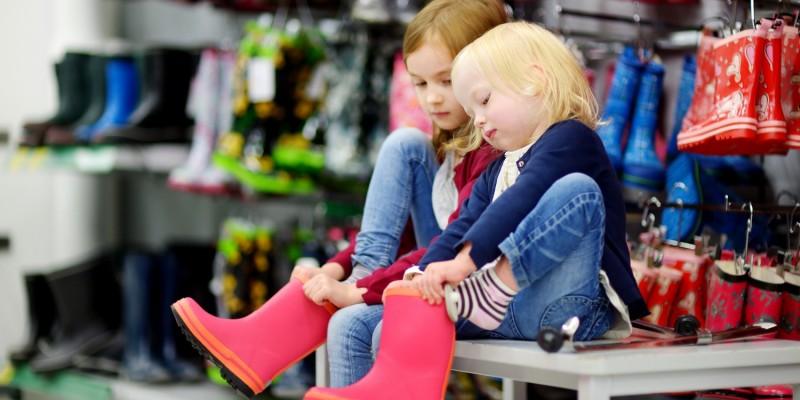 Mädchen probieren im Geschäft Gummistiefel an